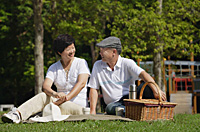 Couple having a picnic in the park - Asia Images Group