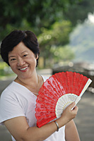 Woman with fan smiling at camera - Asia Images Group