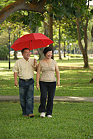 Couple taking a stroll in the park - Asia Images Group