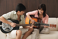 Young couple playing guitar - Asia Images Group