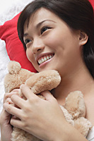 Young woman playing with teddy - Asia Images Group
