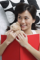 Young woman with teddy and book - Asia Images Group