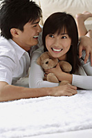 Young couple laughing while hugging and lying on the floor - Asia Images Group