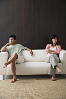 Young couple sitting on opposite ends of the sofa - Asia Images Group