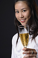 Young woman toasting with champagne and looking at camera - Asia Images Group
