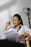 Young woman with paper and pen smiling at camera - Asia Images Group