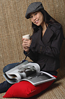Young woman with cup smiling at camera - Asia Images Group