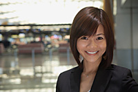 Young woman at the airport, smiling at camera - Asia Images Group