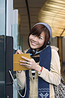 Young woman on public phone at the airport - Asia Images Group