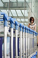 Young woman retrieving trolley at the airport - Asia Images Group
