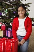 Girl with Christmas presents and Christmas tree at background - Asia Images Group