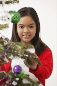 Girl by the Christmas tree, looking at camera - Asia Images Group