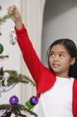 Girl hanging up Christmas decoration to the tree - Asia Images Group