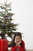 Girl elbow on ground with Christmas present and Christmas tree at the background - Asia Images Group