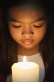 Girl holding and looking at candle - Asia Images Group