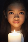Girl holding candle looking at camera - Asia Images Group