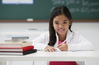 Girl with pen sitting at school desk smiling at camera - Asia Images Group