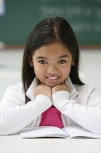 Girl sitting at school desk and smiling at camera - Asia Images Group