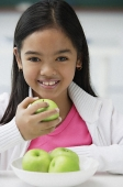 Girl holding green apple in one hand smiling at camera - Asia Images Group