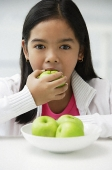 Girl eating green apple - Asia Images Group