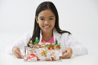 Girl with Christmas log cake smiling at camera - Asia Images Group