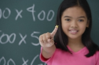 Girl with star on finger standing in front of blackboard - Asia Images Group
