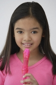 Girl with pink recorder, looking at camera - Asia Images Group