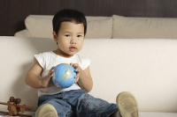 Baby boy holding globe looking at camera - Asia Images Group
