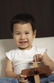 Baby boy holding wooden toy plane smiling at camera - Asia Images Group