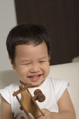 Baby boy playing with wooden toy plane - Asia Images Group