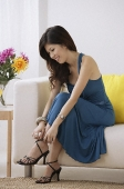 Young woman putting on high heels - Asia Images Group
