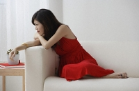 Young woman sitting with legs up on sofa - Asia Images Group