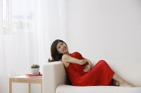 Young woman sitting on sofa - Asia Images Group