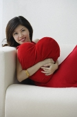 Young woman sitting on sofa with heart-shaped cushion - Asia Images Group