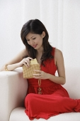 Young woman with purse sitting on sofa - Asia Images Group