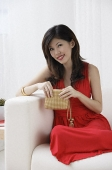 Young woman with purse sitting on sofa smiling at camera - Asia Images Group