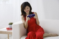 Young woman playing with handheld video console - Asia Images Group