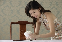Young woman placing bowl of rice on table - Asia Images Group