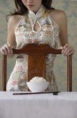 Young woman behind chair with bowl of rice on table - Asia Images Group