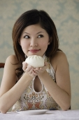 Young woman holding chinese bun with both hands - Asia Images Group