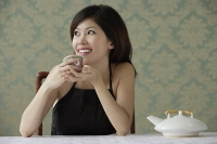 Young woman holding teacup looking sideway - Asia Images Group