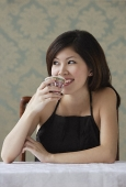 Young woman drinking tea looking sideway - Asia Images Group