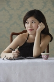 Young woman with journal staring thoughtfully into distance - Asia Images Group