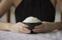Young woman holding bowl of rice with both hands - Asia Images Group