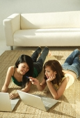 Young women laying on mat using laptops - Asia Images Group