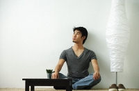 Young man sitting on floor looking up - Asia Images Group