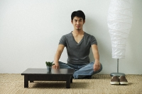 Young man sitting on floor, looking at camera - Asia Images Group