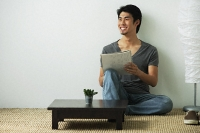 Young man sitting on floor while writing - Asia Images Group