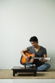 Young man sitting on floor and playing guitar - Asia Images Group