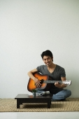 Young man sitting on floor playing guitar smiling at camera - Asia Images Group